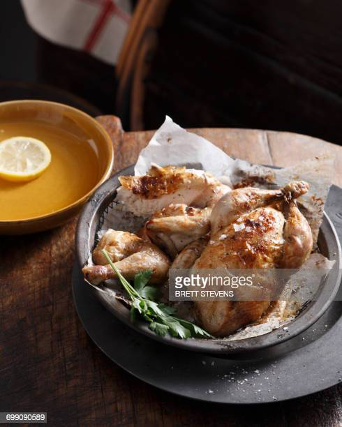 Bistro meal of roast chicken in a basket with parsley on table