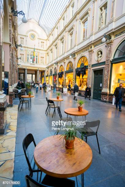 Bistrot table and chairs outside the entrance of a movie theater under the glass-roofed of Galeries Royales Saint-Hubert, one of Arcade galleries in Brussels, Belgium Galeries Royales Saint-Hubert, one of Arcade galleries in Brussels, Belgium