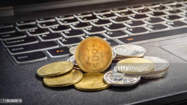 bitcoin and laptop - kryptowährung stock-fotos und bilder