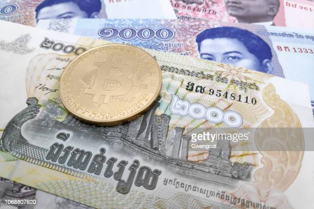 Bitcoin coin on top of a stack of Cambodian Riel banknotes