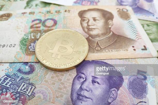 Bitcoin coin on top of a stack of Chinese Yuan banknotes