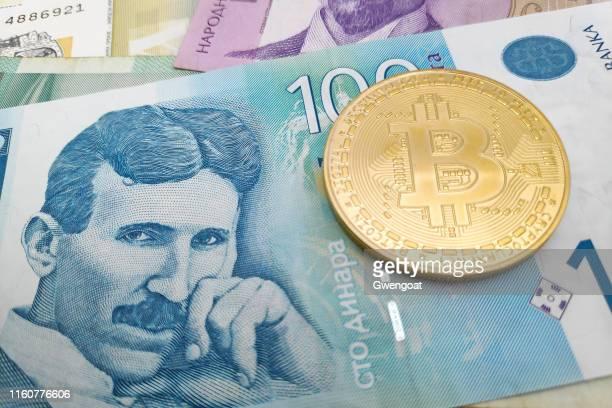 bitcoin-münze auf einem stapel serbischer dinar-banknoten - nikola tesla stock-fotos und bilder
