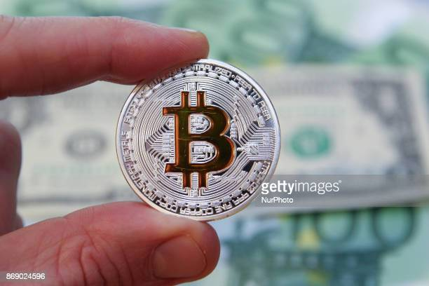Bitcoin cryptocurrency symbolic coin is seen in front of 100 Euro and 1 US Dollar notes in this photo illustration in Gdansk Poland on 1 November...