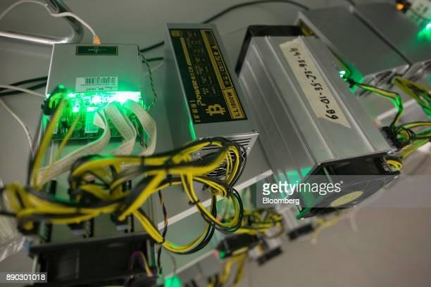 A bitcoin logo sits on a LL 1800W power unit supplying cryptocurrency mining machines at the SberBit mining 'hotel' in Moscow Russia on Saturday Dec...