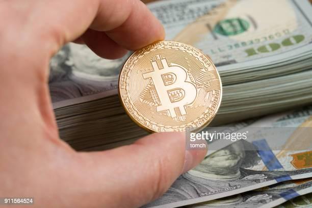 Bitcoin on hand on dollars bill background.