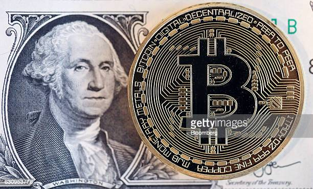 A bitcoin token sits next to the image of George Washington on a US one dollar bill in this arranged photograph in London UK on Wednesday Jan 4 2017...