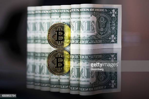 A bitcoin token stands next to a collection of US one dollar bills in this arranged photograph in London UK on Wednesday Jan 4 2017 The electronic...