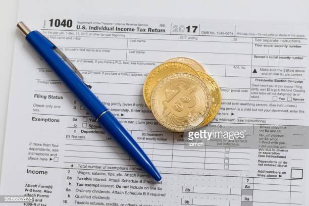 bitcoins and a pen on the tax return - 1040 tax form stock photos and pictures
