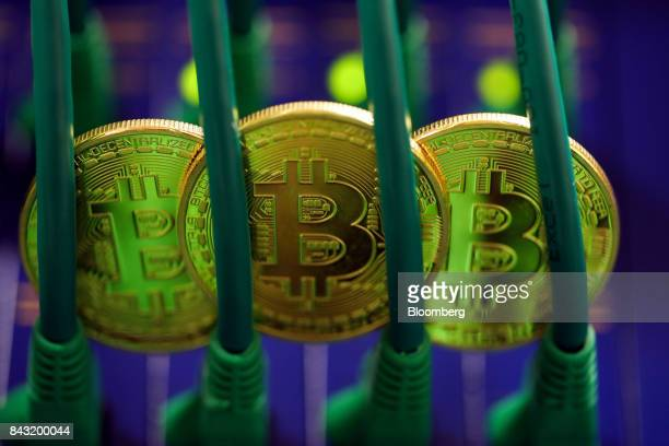 Bitcoins sit among Ethernet cables inside a communications room at an office in this arranged photograph in London UK on Tuesday Sept 5 2017 Bitcoin...