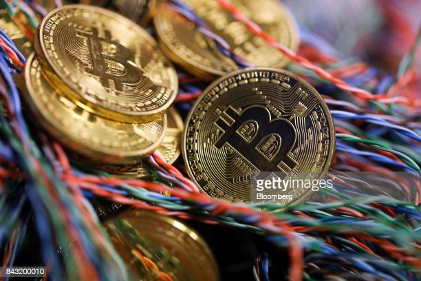 Bitcoins sit among twisted copper wiring inside a communications room at an office in this arranged photograph in London UK on Tuesday Sept 5 2017...