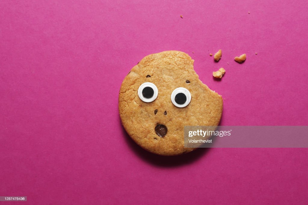 Biten cookie with eyes and frightened face on pink background : Stock Photo