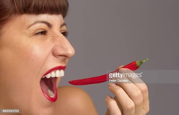 Biting into red chilli pepper