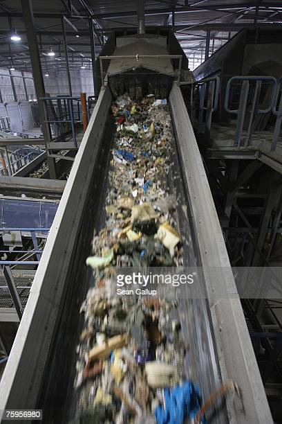 Bits of garbage flow through a conveyor for sorting at a garbage processing center August 3 2007 in Nuemuenster Germany The center known as a...