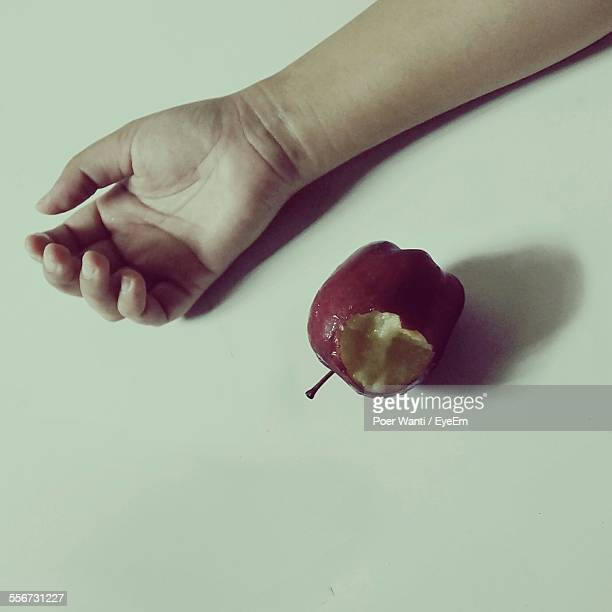 Bitten Apple By Hand Against White Background