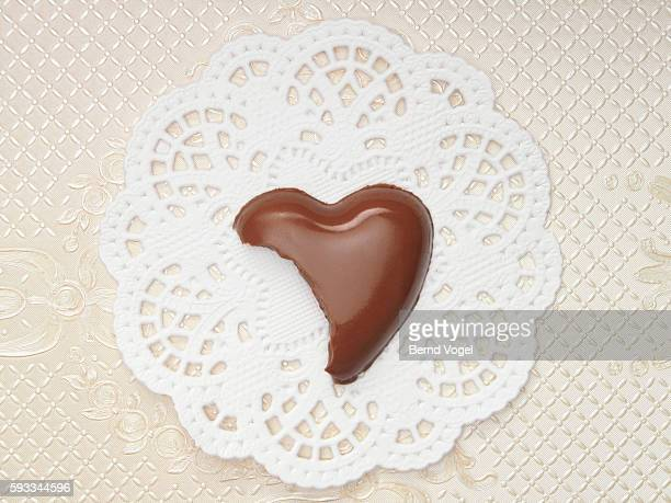 bitten chocolate heart - doily stock photos and pictures