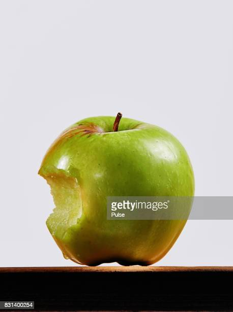 Bitten green apple on wooden surface