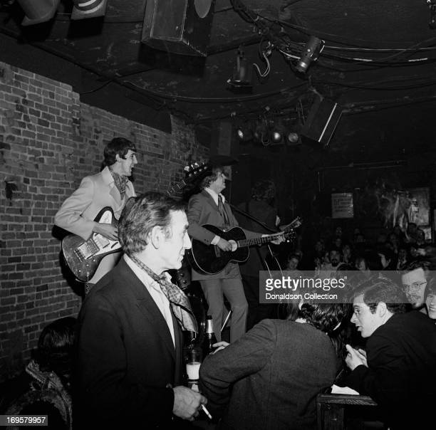Bitter End owner Paul Colby looks on as brothers Don Everly and Phil Everly of the rock and roll group the 'Everly Brothers' perform onstage with...
