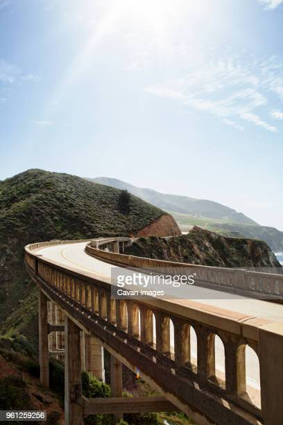 bixby creek bridge and mountains against sky - bixby bridge stock photos and pictures