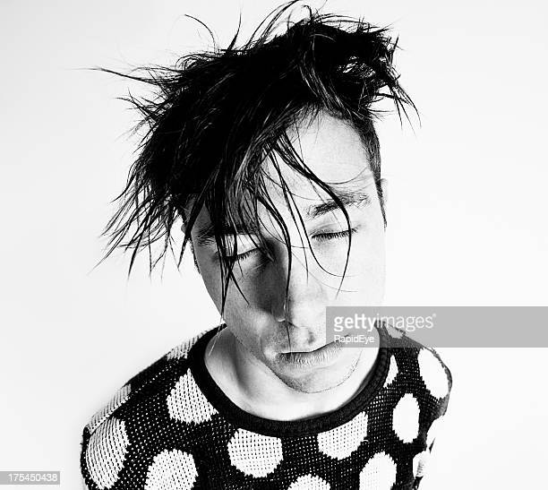 Bizarre looking young man with bedhead hair and closed eyes