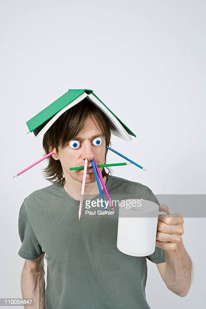 Bizarre man with pencils, book and coffee