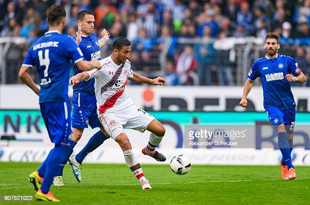 Bjarne Thoelke of Karlsruhe challenges Aziz Bouhaddouz of St. Pauli during the Second Bundesliga match between Karlsruher SC and FC St. Pauli at...