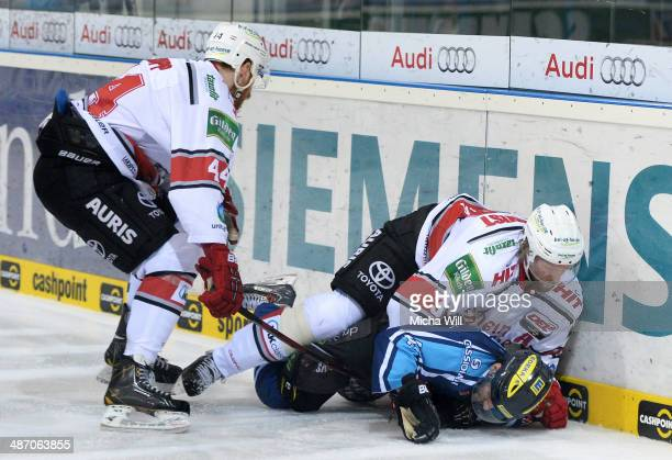 Bjoern Krupp and Daniel Tjaernqvist of Koeln battle with Jared Ross of Ingolstadt for the puck in game six of the DEL final playoffs between ERC...