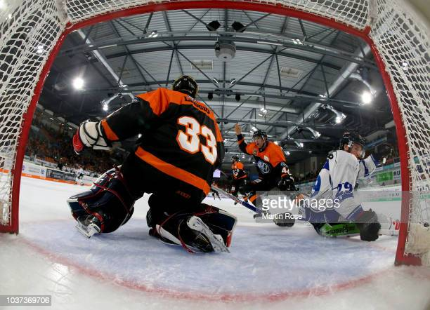 Bjoern Krupp of Wolfsburg and Mitchel Heard of Straubing battle for the puck during the DEL match between Grizzlys Wolfsburg and Straubing Tigers at...