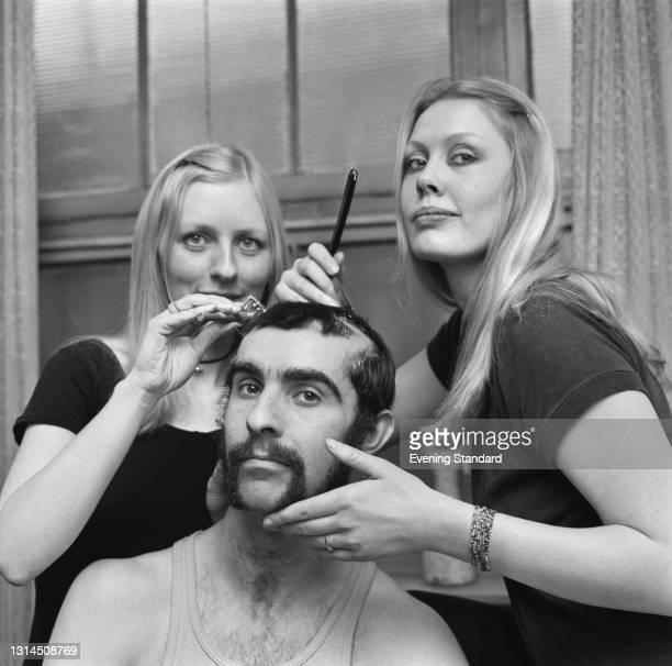 Bjorg Arnadottir and Inge Bjornsson grooming English guitarist Nigel Watson , UK, 5th February 1974.