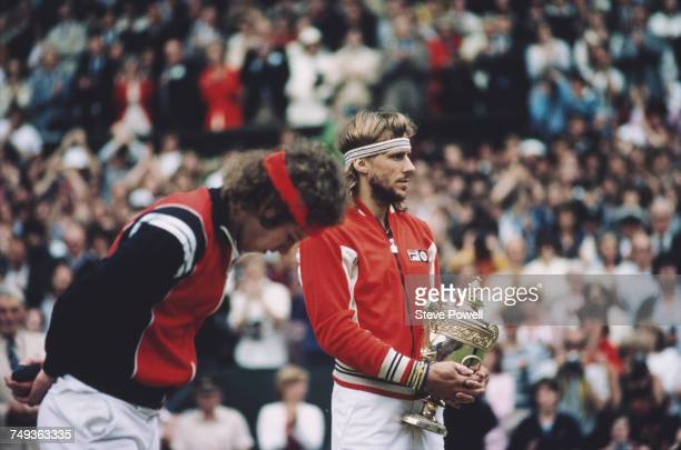 Bjorn Borg of Sweden holds the Gentleman's Singles trophy as John McEnroe looks down after losing their Men's Singles Final match at the Wimbledon...