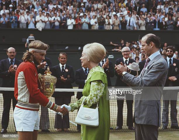 Bjorn Borg of the Sweden receives the trophy from the Duke and Duchess of Kent after defeating Roscoe Tanner during the Men's Singles Final match at...
