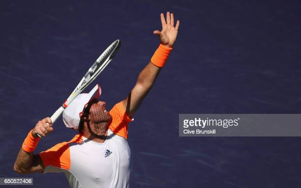 Bjorn Fratangelo of the United States serves against Bernard Tomic of Australia in their first round match during day four of the BNP Paribas Open at...