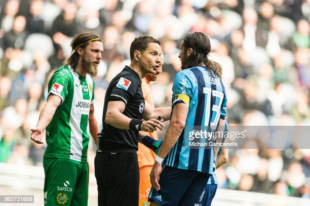 Bjorn Paulsen of Hammarby IF and Jonas Olsson of Djurgardens IF argue in front of referee Martin Strombergsson during a match between Djurgardens IF...