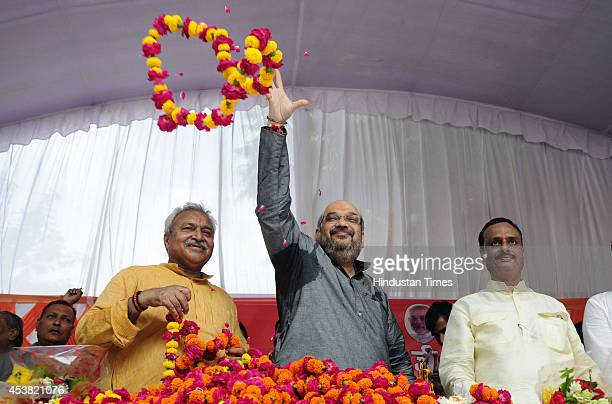 BJPs national president Amit Shah showering flowers on party workers along with state president L K Bajpai and vice-president Dr Dinesh Sharma on his...