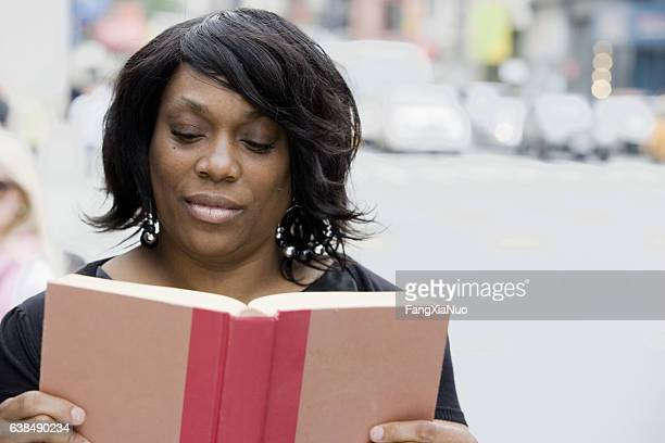 Black adult woman reading story book in downtown city