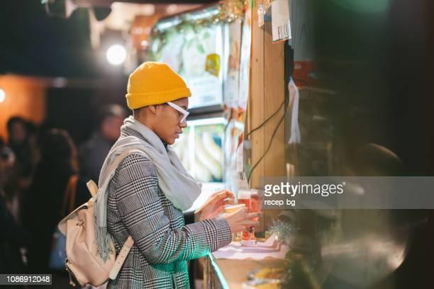 black african american woman kauf von getränken am marktstand - one night stand stock-fotos und bilder