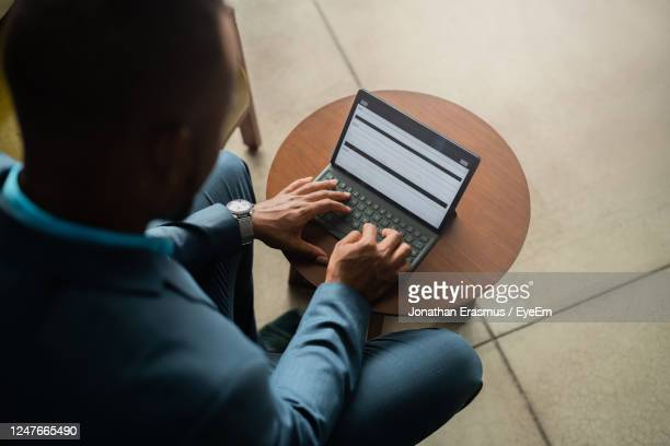 black african businessman typing on a digital tablet computer with attached keyboard - human body part stock pictures, royalty-free photos & images