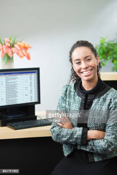 black african decent bank teller working behind bank counter at retail bank - bank financial building stock pictures, royalty-free photos & images
