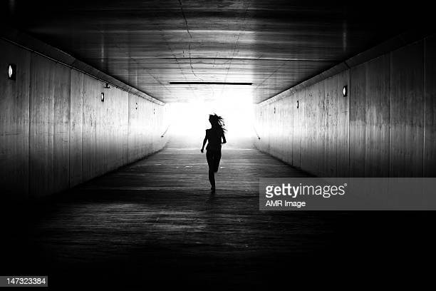black amd white image of girl running towards the light - silhouette stock pictures, royalty-free photos & images