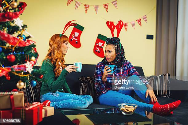 Black and ginger women drinking tea at home for Christmas
