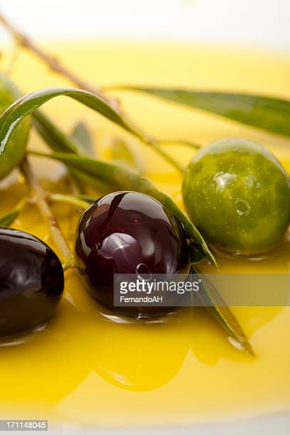 black and green olives in olive oil background - kalamata olive stock photos and pictures