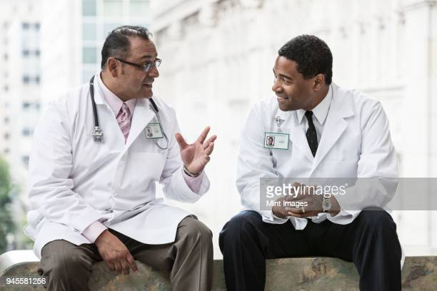 Black and Hispanic male doctors discussing a case in a hospital hallway.