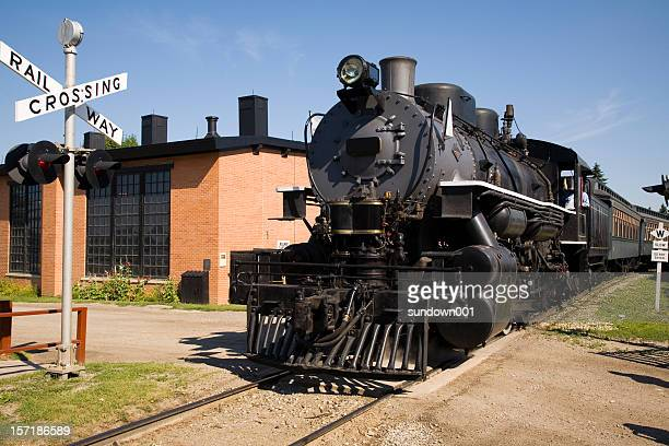 a black and large steam train going through a crossing  - cowcatcher stock pictures, royalty-free photos & images