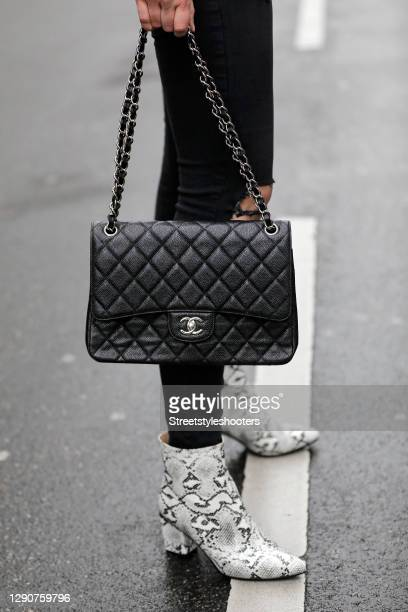 Black and white ankle boots with snake pattern by Basso and a black and silver flap bag by Chanel as a detail of german model and actress Victoria...