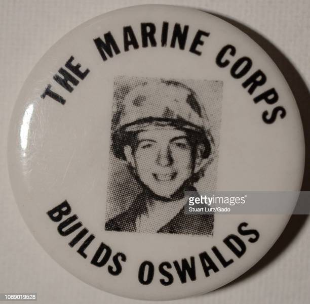Black and white anti-war pin or button with a headshot of President John F Kennedy's assassinator, Lee Harvey Oswald, wearing a helmet and uniform,...