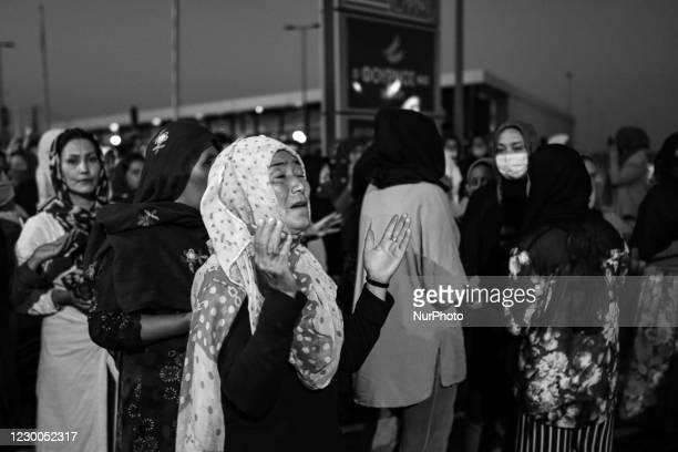 Black and White B/W photo of hundreds of women and girls are seen praying on the road after the sunset, at the makeshift tent site that was built...
