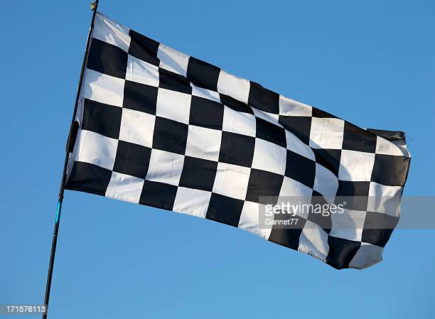 Black and white checkered flag flying against blue sky