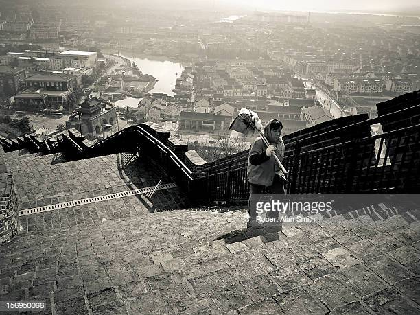 black and white cityscape showing the walled city of Changshu in China with a street cleaner climbing the steps of the inclined wall with the city in...