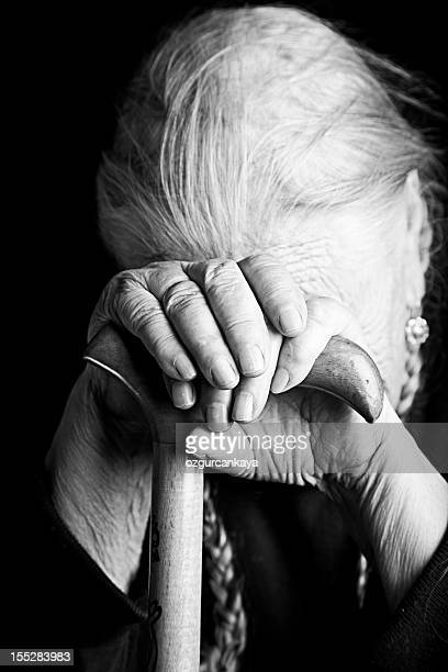 Black and white close-up photo of elderly woman holding cane