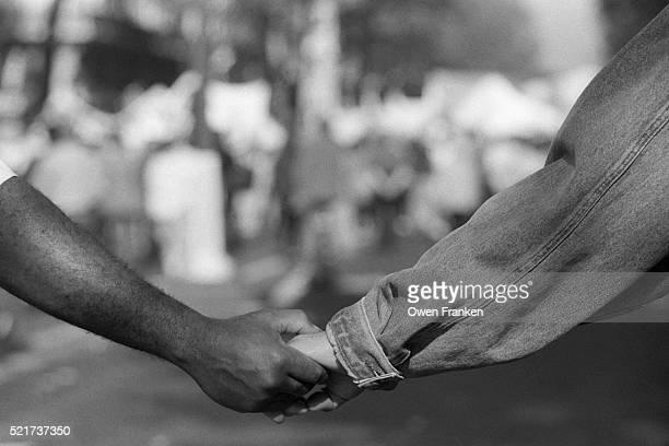 black and white demonstrators hold hands - racism stock pictures, royalty-free photos & images