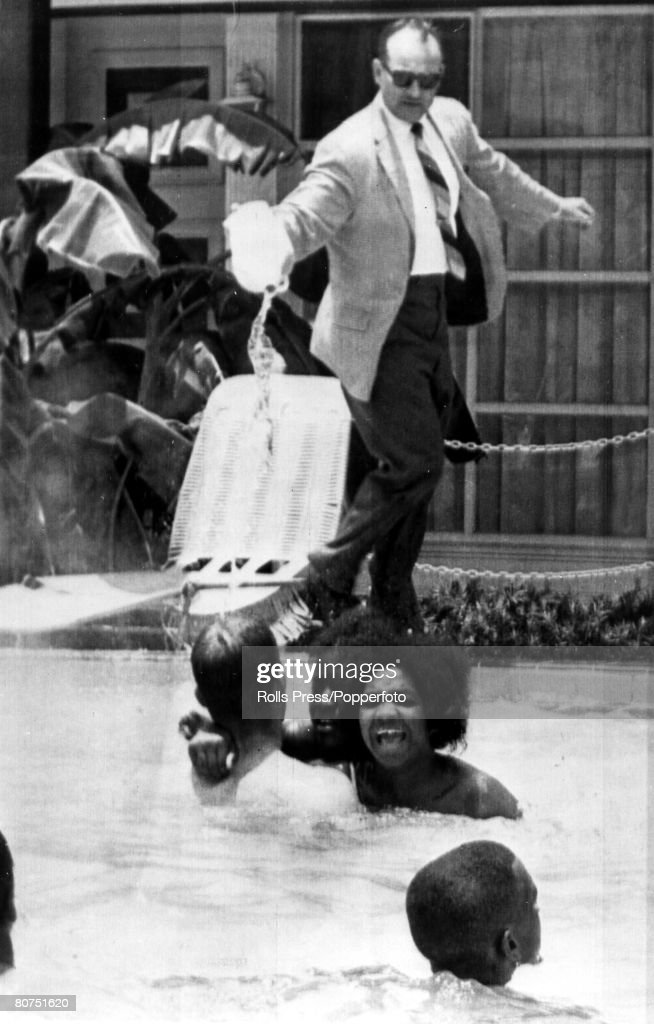 Black and white demonstrators stage a 'jump-in' at the Monson Motor Lodge pool, open only to whites, as the angry motel manager James Brock dumps the contents of two containers marked 'muriatic acid' into the pool, which hastened their departure on June 18, 1964 in St. Augustine, Florida.